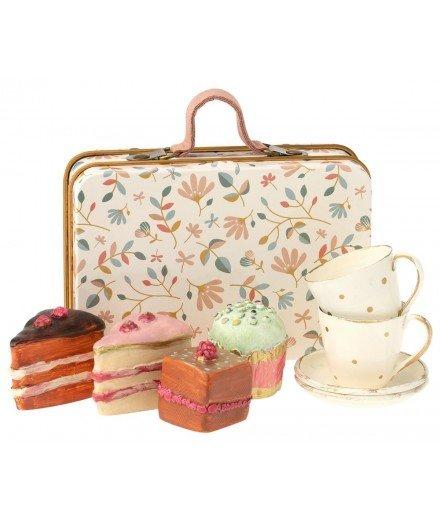 Valise motif floral avec gâteaux et tasses à thé